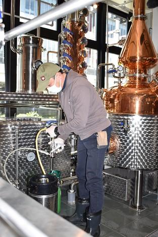ビールをタンクに入れ、作業スタッフの後ろに見えている蒸留窯に送り込む(筆者撮影)