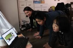 地域限定SNSアプリ「ピアッザ」の矢野晃平社長の運動動画を見ながら体を動かす木村千代子さん(左)と子どもたち=東京都中央区で2020年4月20日、後藤豪撮影