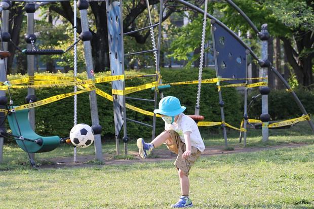 使用禁止となった遊具の近くでボール遊びをする男の子=東京都江東区で2020年4月29日、幾島健太郎撮影