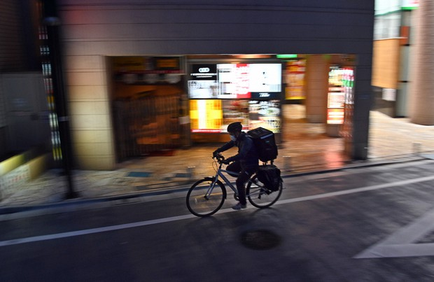 外出自粛が呼びかけられる東京都内で、飲食店から注文客の家まで料理を運ぶ配達員の男性。新型コロナウイルスの影響でデリバリーサービスの需要が高まっており、この男性も多い日で1日二十数件を請け負うという=東京都豊島区で2020年4月29日、北山夏帆撮影