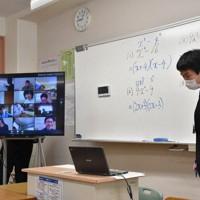 一斉休校を受け、インターネットを介した遠隔授業の実験に取り組む田中信行教諭と、モニター(左)に映し出された自宅の生徒たち=鳥取県岩美町立岩美中で、阿部絢美撮影