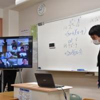 一斉休校を受け、インターネットを介した遠隔授業の実験に取り組む田中信行教諭と、モニター(左)に映し出された自宅の生徒たち=岩美町立岩美中で、阿部絢美撮影