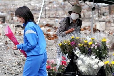 周囲に多くのがれきが残る駐車場に、テントを張っただけの仮設の花屋さんが店を再開。店頭には母の日のために、色とりどりのカーネーションをそろえた。遺族を思い白いカーネーションも並べた。白いカーネーションを買い求めた少女=岩手県山田町で2011年5月8日午後1時13分、三浦博之撮影