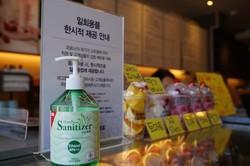 一時的に使い捨てコップを使うとする案内文。消毒液と一緒に置かれていた=ソウル市内で2020年3月18日、渋江千春撮影