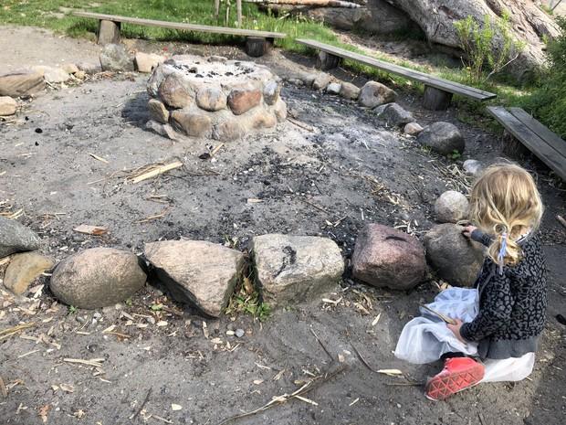 料理などをする火起こし場にて、落ちている炭で絵を描けることに気づき没頭している子(2019年筆者撮影)