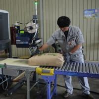 福島県産米の放射性物質を調べるため実施されている全量全袋検査=同県二本松市で2015年8月20日、横田香奈撮影