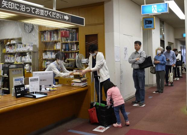 久しぶりの開館で一度に多くの本を借りる利用者。カウンターにはビニールシートが設置されている=岡山市北区二日市町の岡山市立中央図書館で2020年5月9日午前10時30分、松室花実撮影