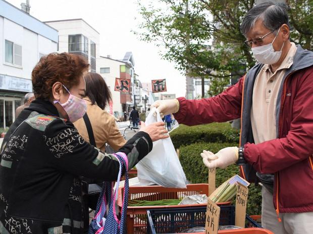 マスクをしながら、露店が並ぶイベント「よ市」での買い物を楽しむ人たち=盛岡市材木町で2020年5月9日午後3時42分、三瓶杜萌撮影