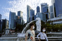 In this March 14, 2020, photo, a couple wearing face masks walk past the Merlion statue in Singapore. (AP Photo/Ee Ming Toh)