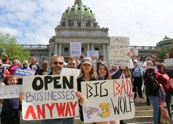 州議会議事堂前でプラカードを掲げ外出制限に抗議するデモ参加者ら=米東部ペンシルベニア州ハリスバーグで1日、高本耕太撮影