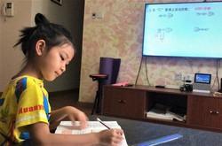 自宅でテレビモニターに向かい、オンライン授業を受ける崔嘉淇さん=中国・南寧市で2020年5月11日、家族提供