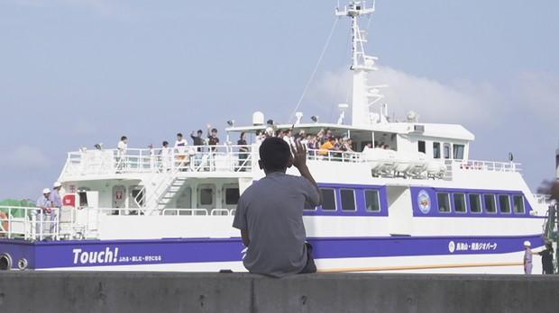 島で唯一の中学生、渋谷新くんの後ろ姿。夏の間、飛島に来ていた友人たちを港で見送る