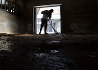 A zookeeper cleans a floor covered with dung at Osaka Tennoji Zoo in Osaka's Tennoji Ward, on April 23, 2020. (Mainichi/Ryoichi Mochizuki)