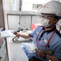 政府の布マスクを集合住宅に届ける配達員=福岡市中央区で5月12日午前9時35分、津村豊和撮影