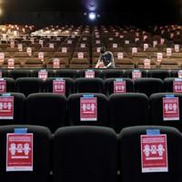 緊急事態宣言が解除された新潟県内で営業再開した映画館で、上映後に客席をアルコール消毒するスタッフ。座席には距離を保つための注意書きが張られていた=新潟市中央区の「ユナイテッド・シネマ新潟」で2020年5月15日午後0時45分、佐々木順一撮影