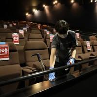 営業再開した映画館「ユナイテッド・シネマ新潟」で上映後、客席をアルコール消毒するスタッフ。座席には距離を保つための注意書きが張られていた=新潟市中央区で2020年5月15日午後0時44分、佐々木順一撮影
