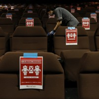 営業再開した映画館「ユナイテッド・シネマ新潟」で上映後、客席をアルコール消毒するスタッフ。座席には距離を保つための注意書きが張られていた=新潟市中央区で2020年5月15日午後0時47分、佐々木順一撮影