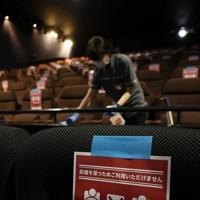 営業再開した映画館「ユナイテッド・シネマ新潟」で上映後、客席をアルコール消毒するスタッフ。座席には距離を保つための注意書きが張られていた=新潟市中央区で2020年5月15日午後0時46分、佐々木順一撮影