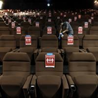 営業再開した映画館「ユナイテッド・シネマ新潟」で上映後、客席をアルコール消毒するスタッフ。座席には距離を保つための注意書きが張られていた=新潟市中央区で2020年5月15日午後0時48分、佐々木順一撮影
