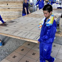 宮城県石巻市の避難所へ届ける選挙ポスター掲示板を運ぶサッカー部員=宮崎市で2011年5月21日、石田宗久撮影