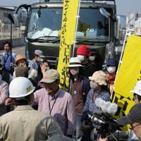 宮城県からの震災がれきを積んだトラックを止め、市職員(手前の白いヘルメット)とにらみ合う市民グループ=北九州市小倉北区で2012年5月22日午前9時16分、上入来尚撮影