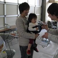 母親に抱かれてスクリーニングを受ける女児=福島市御山町の県北保健福祉事務所で2011年5月24日、仙石恭撮影
