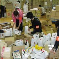 震災復興イベントで配布する支援物資の袋詰め作業に汗を流す学生ボランティア=茨城県高萩市で2011年5月24日、臼井真撮影