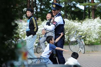 避難所の前で警察官と遊ぶ子供たち=岩手県宮古市で2011年5月27日午後3時12分、兵藤公治撮影