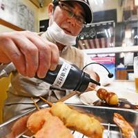 「二度漬け禁止」の共用のソース容器が撤去され、ボトル入りのソースをかける男性=大阪市中央区の串かつだるま道頓堀店で2020年5月18日午後5時45分、山崎一輝撮影