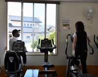 An owner of a sports gym in Nagano Prefecture is seen talking to a customer while maintaining a distance and opening a window to ventilate the room on May 7, 2020. (Mainichi/Masahito Minagawa)