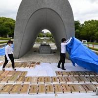 原爆慰霊碑の前で原爆死没者名簿の「風通し」をする広島市職員ら。途中で雨が降り出し、カバーをかける場面も見られた=広島市中区で2020年5月20日午前9時18分、山田尚弘撮影