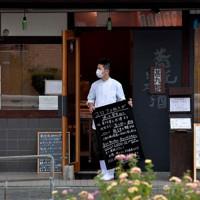 学生に呼び掛ける看板を店前に出す森本さん=大阪市淀川区で2020年5月18日、平川義之撮影