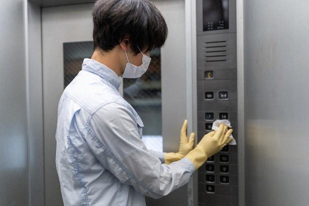 エレベーターのボタンをふく男性