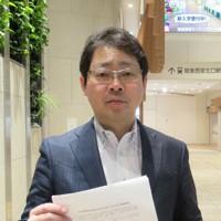 新型コロナウイルス感染への災害法制の応用を訴える緊急提言を手にする津久井進弁護士=兵庫県西宮市で
