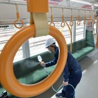 JR大阪環状線車両で公開された抗ウイルス・抗菌液の吹き付け作業=大阪市城東区で2020年5月22日午前9時56分、望月亮一撮影