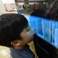 本の殺菌消毒やゴミくずの除去などができる「図書消毒機」を使う児童=奈良県の桜井市立図書館で2020年5月18日、藤井達也撮影