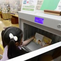 本の殺菌消毒やゴミくずの除去などができる図書消毒機を使う児童=奈良県の桜井市立図書館で2020年5月18日、藤井達也撮影
