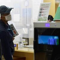 本の殺菌消毒やゴミくずの除去などができる図書消毒機を利用する人たち=奈良県の桜井市立図書館で2020年5月18日、藤井達也撮影