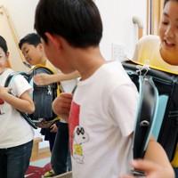 鏡の前で新品のランドセルを背負う折橋明さん(手前)と兄光さん=仙台市若林区で2020年5月5日、和田大典撮影