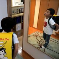 鏡の前で新品のランドセルを背負う折橋明さん=仙台市若林区で2020年5月5日、和田大典撮影