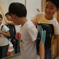 鏡の前で新品のランドセルを背負う折橋明さん(左)と兄光さん=仙台市若林区で2020年5月5日、和田大典撮影