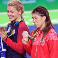レスリング女子53㌔級の表彰後、銀メダルを手に涙ぐむ吉田沙保里選手(手前)と笑顔で金メダルを掲げる米国のヘレン・マルーリス選手=リオデジャネイロのカリオカアリーナで2016年8月18日、梅村直承撮影