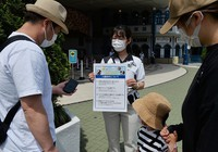 A staff member confirms visitors' IDs and online tickets, among other conditions, at Adventure World amusement park, which partly resumed operations after closing due to the novel coronavirus pandemic, in Shirahama, Wakayama Prefecture, on May 21, 2020. (Mainichi/Takao Kitamura)