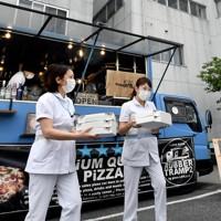 キッチンカーで届けられた焼き立てのピザを受け取り、笑顔を見せる病院の職員ら=千葉市緑区の千葉南病院で2020年5月18日