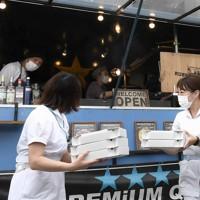 キッチンカーで届けられた焼き立てのピザを受け取り、笑顔を見せる病院の職員ら=千葉市緑区の千葉南病院で2020年5月18日、竹内紀臣撮影