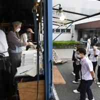 新型コロナウイルス感染拡大の中でも仕事を休めない人に感謝と温かい食事を届けたいと、キッチンカーで届けられるピザを待つ病院の職員ら=千葉市緑区の千葉南病院で2020年5月18日、竹内紀臣撮影