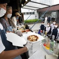 新型コロナウイルス感染拡大の中でも仕事を休めない人に感謝と温かい食事を届けたいと、キッチンカーで届けられるピザを待つ病院の職員=千葉市緑区の千葉南病院で2020年5月18日、竹内紀臣撮影