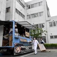 新型コロナウイルス感染拡大の中でも仕事を休めない人に感謝と温かい食事を届けたいと、キッチンカーで届けられたピザを選ぶ病院の職員=千葉市緑区の千葉南病院で2020年5月18日、竹内紀臣撮影