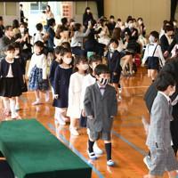 保護者らが見守る中、入学式でマスクを着けて入場する新1年生=福岡市中央区の市立赤坂小で2020年5月23日午前9時、矢頭智剛撮影