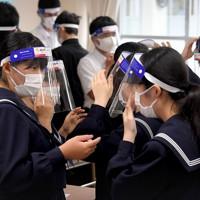 フェースシールドを装着して教室で過ごす生徒たち=福岡県粕屋町の粕屋中学校で2020年5月25日午前8時40分、津村豊和撮影